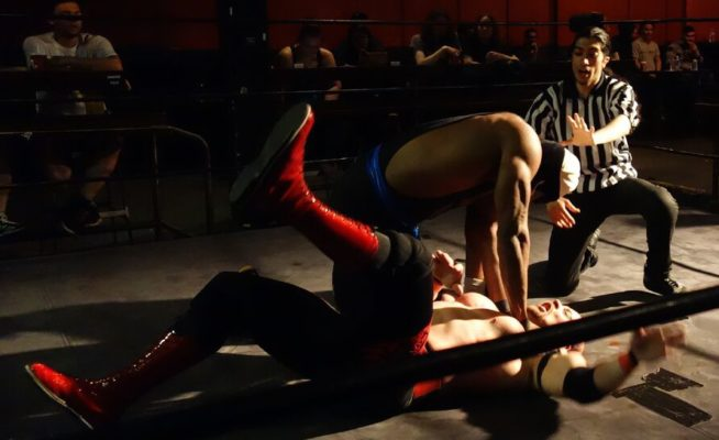 wrestler choking his opponent in the ring